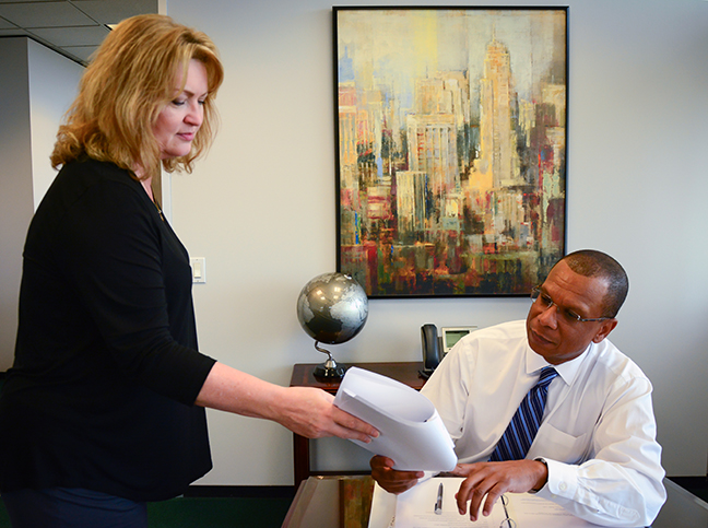 Angela Dinwiddie, executive assistant to Ronald Lewis, hands the City Attorney some papers.