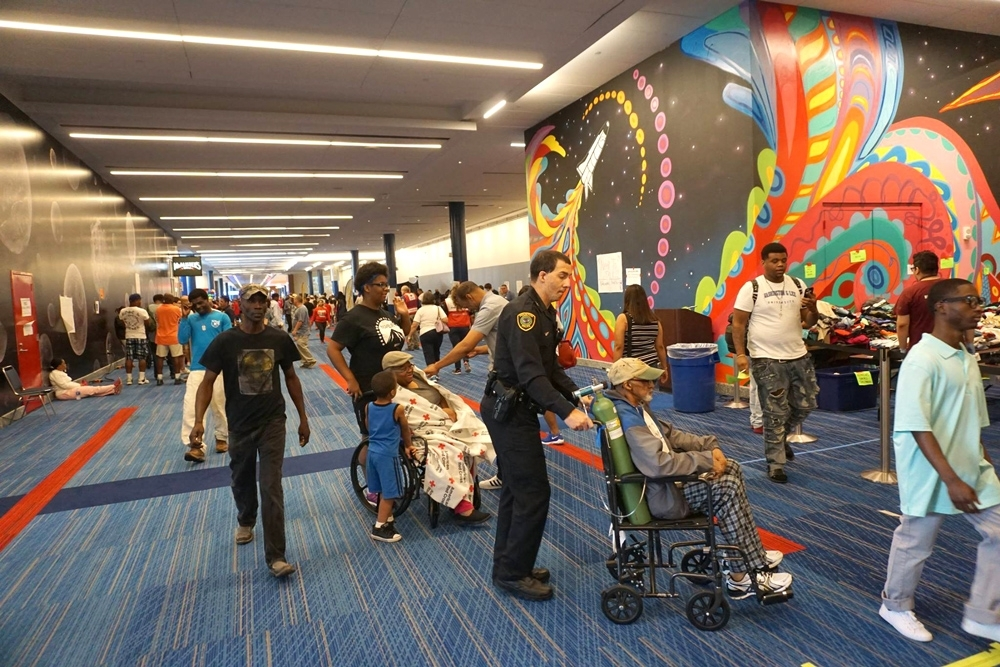 An HPD officer wheels an elderly man into the shelter at the George R. Brown Convention Center.