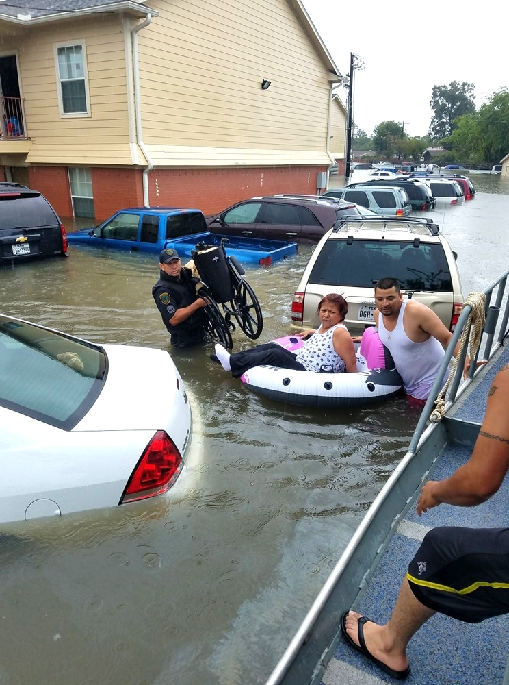 HPD officers rescue a woman from high water and bring her wheelchair.