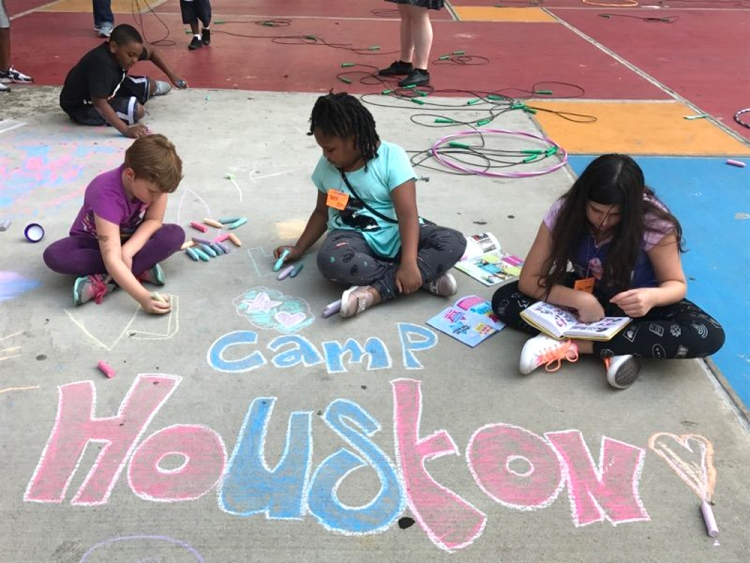 Children of employees draw with chalk in the Central Library plaza during camp HoUSton.