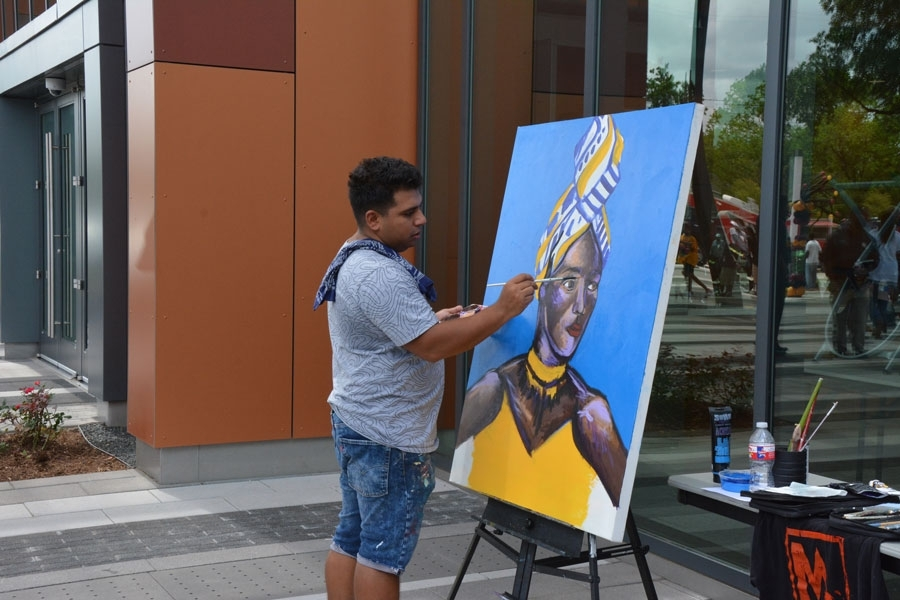A young man paints a portrait of a young woman in an Afrian-inspired head wrap.