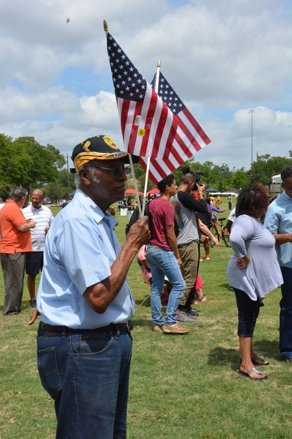John Taylor holds American flags during the Emancipation Park rededication ceremony.