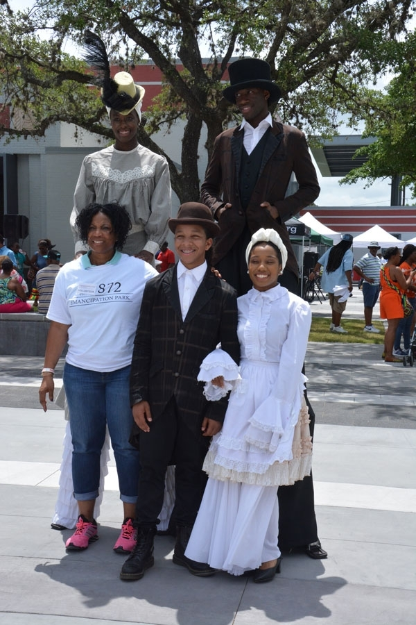 A volunteer poses with performers dressed in early 20th century costumes.
