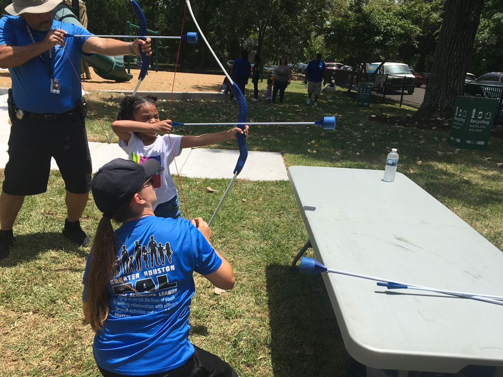Little-girl-being-taught-how-to-shoot-a-bow-and-arrow