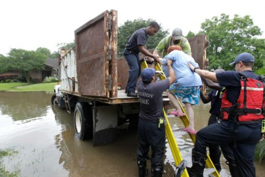 Houston Fire Dept. and other City of Houston personnel load a walker after helping Barbara Levin into a City of Houston dump truck after her house near South Braeswood and Rice was flooded with several feet of water Tuesday, May 26, 2015, in Houston. She was transported to dry land at a staging area nearby. ( Melissa Phillip / Houston Chronicle )