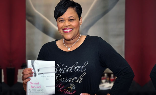 "Norma Jarrett's writing career is no novelty. Besides her career in contract administration with the city's Department of Health and Human Services, she is also a serious author. Above she holds a copy of her latest work, ""Bridal Brunch,"" at a May book signing at Robbins Brothers jewelry store."