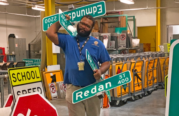 Torian Jerome carries newly minted street signs across the Houston Public Works Sign Fabrication Shop located at 2200 Patterson Road.