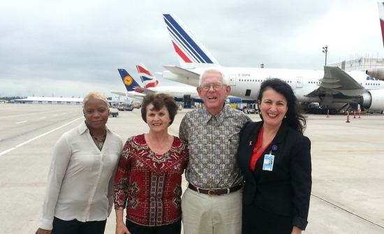 Houston Airport System volunteers Michelle Wall, Lyn and Hutch Hutchings stand on the IAH tarmac with HAS volunteer coordinator Ella Ghica.