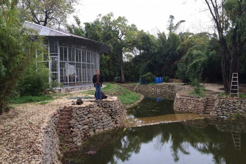 Houston artist Nestor Topchy poses with the eco-pond he built with salvaged concrete from the Reuse Warehouse.