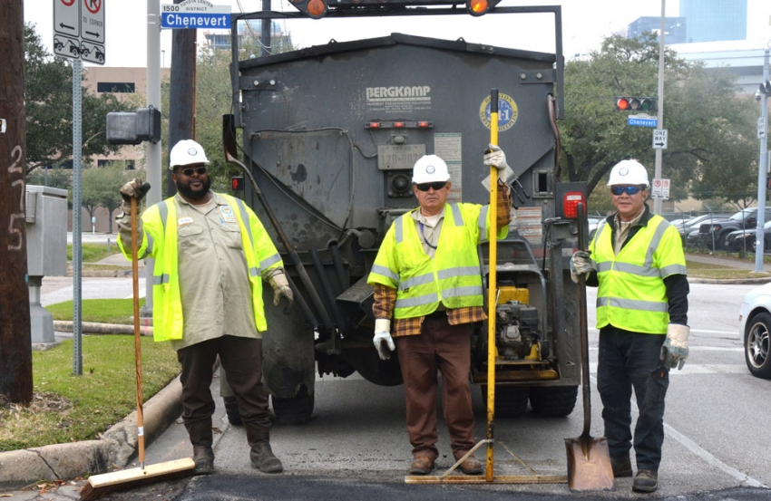 Houston Public Works employees Robert Poole, Fidel Alfaro and Hieu Nguyen complete a pothole repair near downtown Houston.