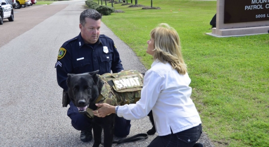 Senior Officer Greg Smith and his partner, Gunnar, greet Susie Jean, whose organization donated safety vests for HPD canine officers.