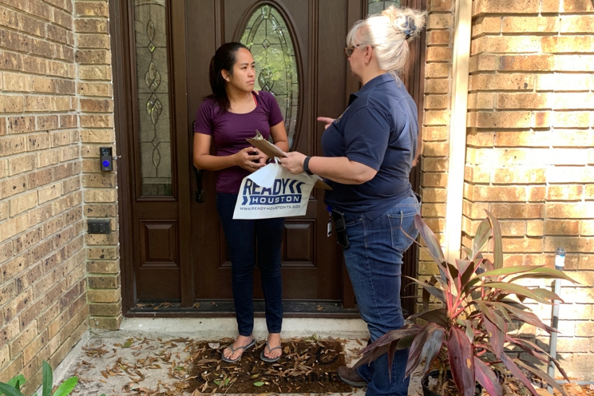 Rhonda Sauter gathers flood damage information from a Kingwood resident whose home was flooded.