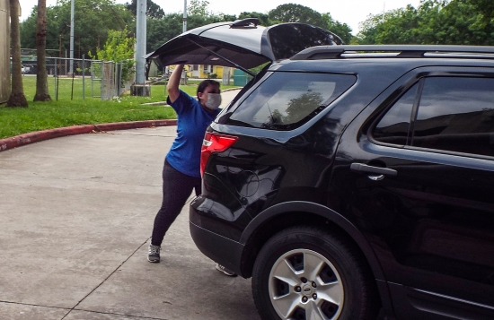 The Houston Parks and Recreation Department created a new curbside drive-through offering to distribute about 1,500 meals a day. Here, HPARD's Amanda Ramos places meals in the back of a participant's vehicle.